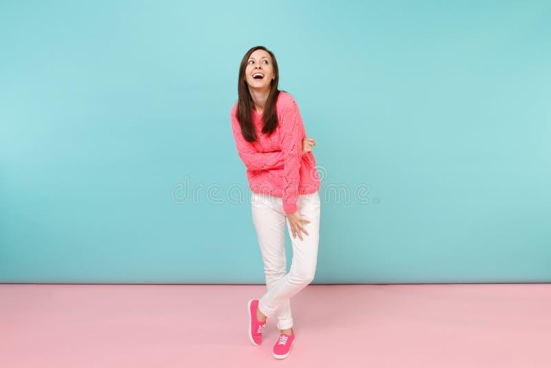 Retrato completo do comprimento da jovem mulher de sorriso na camiseta cor-de-rosa feita malha, levantamento branco das calças is foto de stock