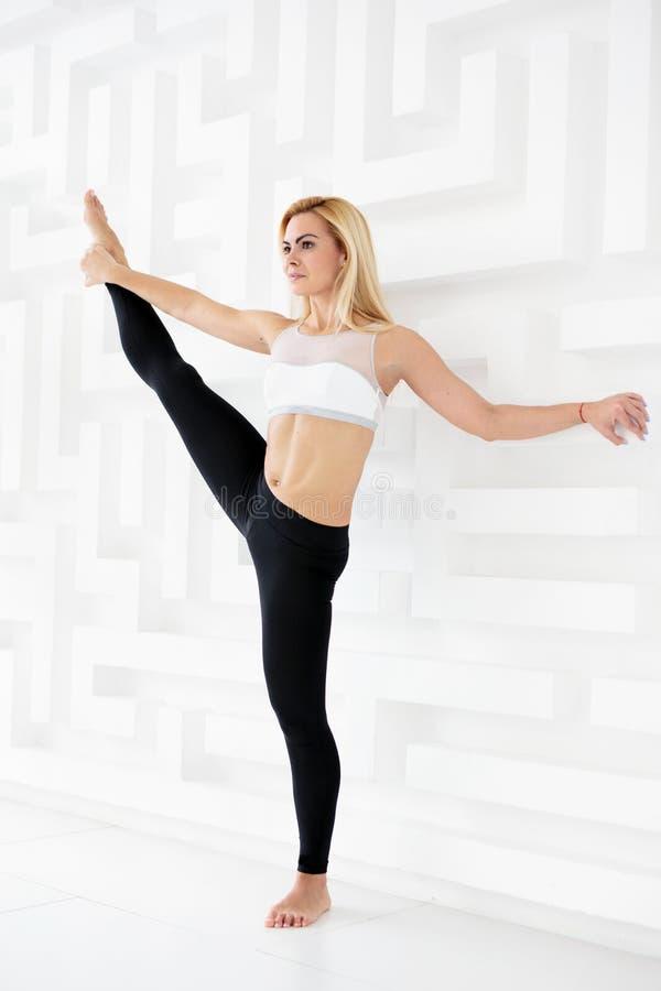 Retrato completo do comprimento da jovem mulher que faz uma pose da ioga que está com o um pé levantado acima fotos de stock