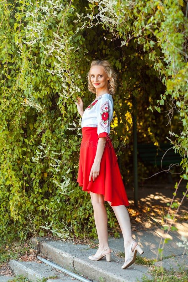 Retrato completo do comprimento da mulher atrativa no vestido branco vermelho à moda que levanta perto do arco floral no jardim e fotografia de stock