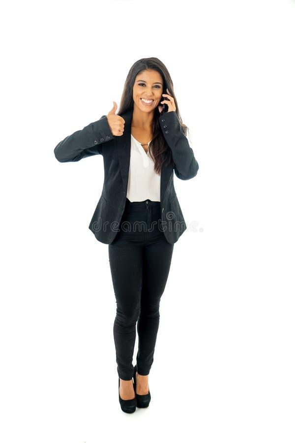 Retrato completo do comprimento da mulher incorporada do latino do latino atrativo em seu polegar entusiasmado e fazendo móvel ac imagem de stock