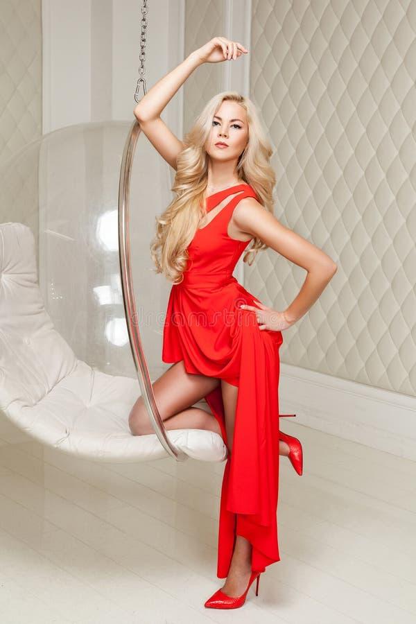 Retrato completo do comprimento da mulher loura lindo sensual no vestido vermelho brilhante com a composição e o penteado encarac imagens de stock