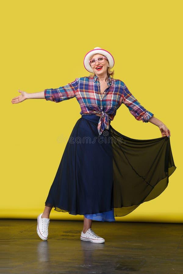 Retrato completo do comprimento da mulher madura à moda bonita feliz no estilo ocasional com o chapéu e os monóculos que estão, l fotografia de stock