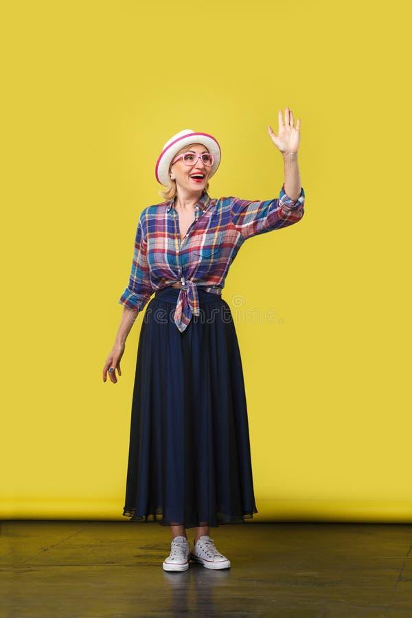 Retrato completo do comprimento da mulher madura à moda moderna entusiasmado no estilo ocasional com o chapéu, a posição dos monó fotografia de stock