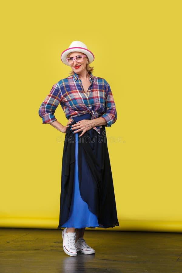 Retrato completo do comprimento da mulher madura à moda moderna feliz bonita no estilo ocasional com o chapéu e os monóculos que  imagens de stock royalty free