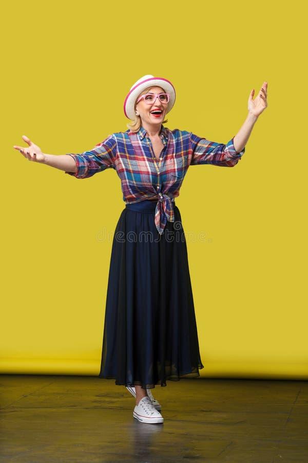 Retrato completo do comprimento da mulher madura à moda moderna feliz no estilo ocasional com o chapéu e os monóculos que estão c imagens de stock royalty free