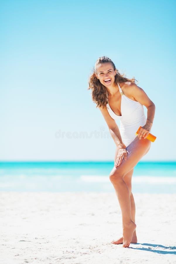 Retrato completo do comprimento da mulher que aplica a nata da tela de sol imagens de stock royalty free