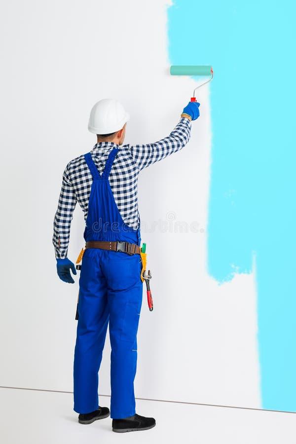 Retrato completo do comprimento da opinião traseira o homem do pintor que pinta o wa imagem de stock royalty free