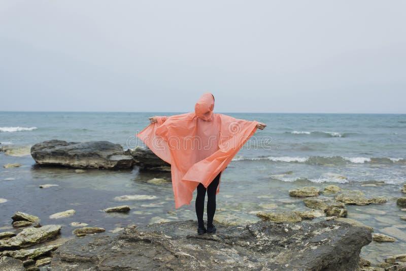 Retrato completo do comprimento da pessoa fêmea na capa de chuva que está com braços estendido em uma rocha de pedra perto do mar imagens de stock