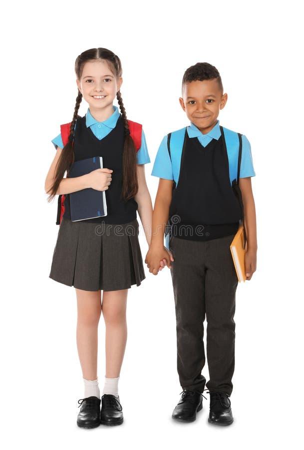 Retrato completo do comprimento de crian?as bonitos na farda da escola com os livros no branco fotografia de stock