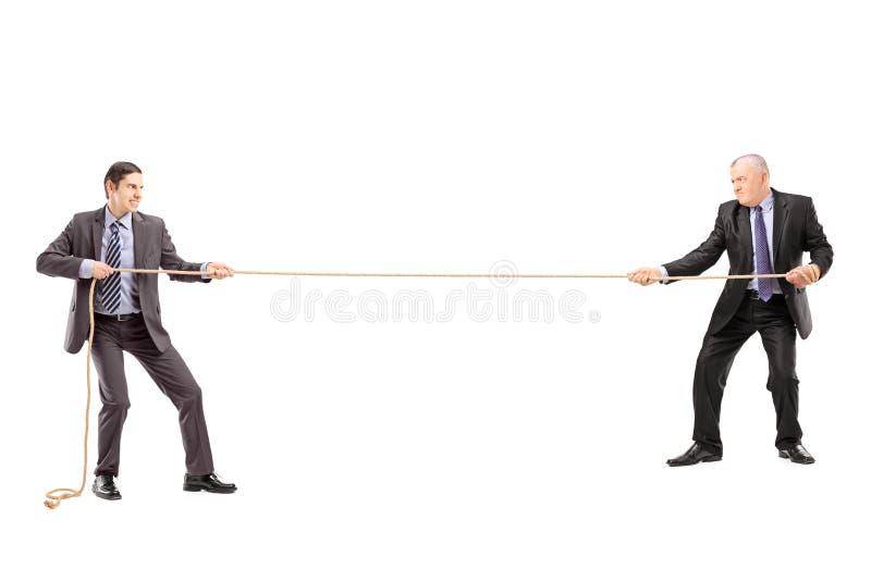 Retrato completo do comprimento de dois homens de negócios que puxam uma corda imagens de stock royalty free