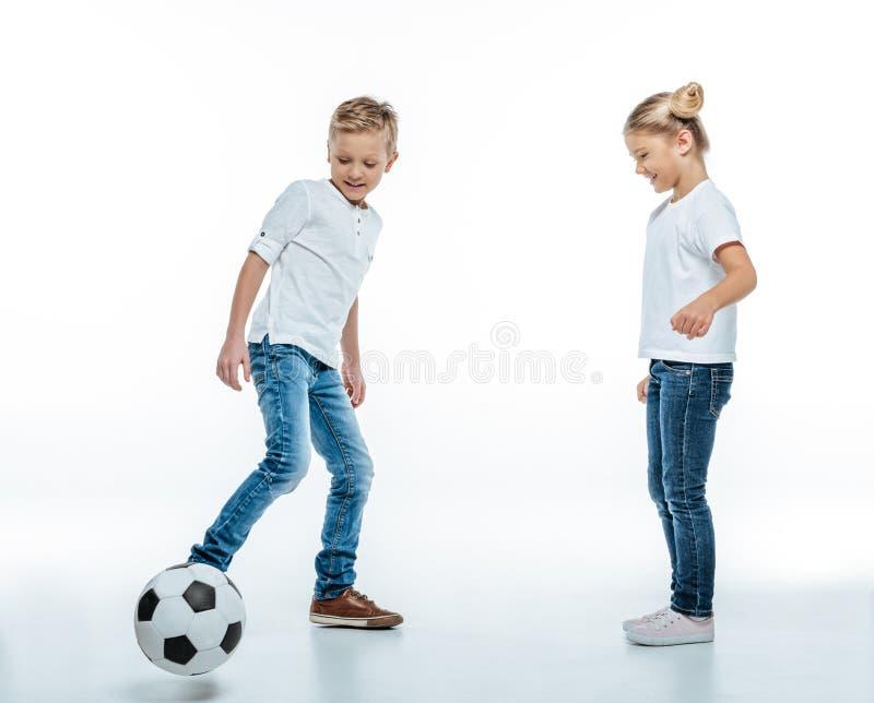 Retrato completo do comprimento de duas crianças de sorriso nos t-shirt brancos e nas calças de brim que jogam com bola de futebo imagens de stock