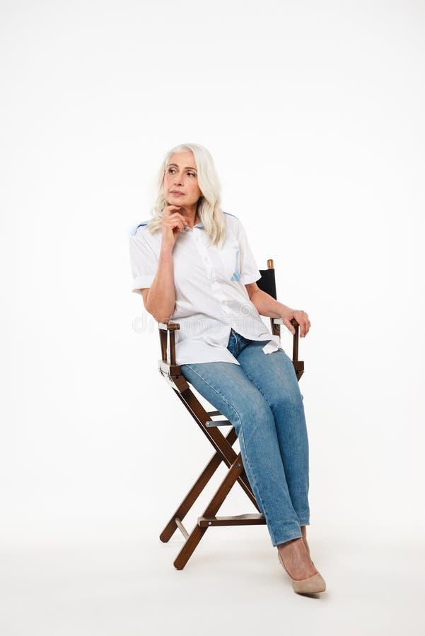 Retrato completo do comprimento de um assento maduro pensativo da mulher imagem de stock royalty free
