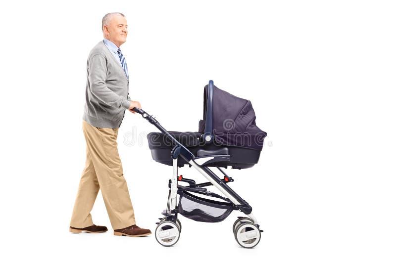 Retrato completo do comprimento de um avô que empurra seu sobrinho do bebê para dentro imagens de stock