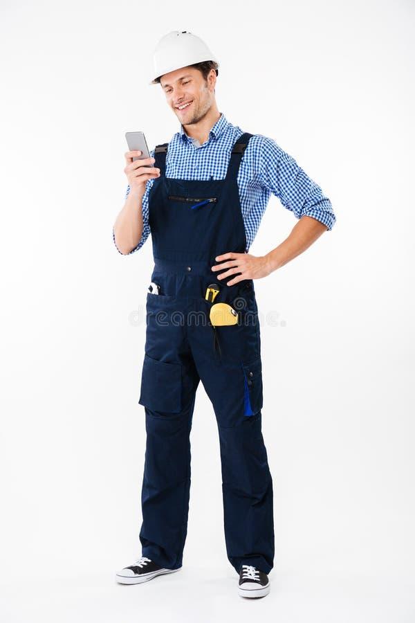 Retrato completo do comprimento de um construtor que está e que usa o telefone foto de stock royalty free