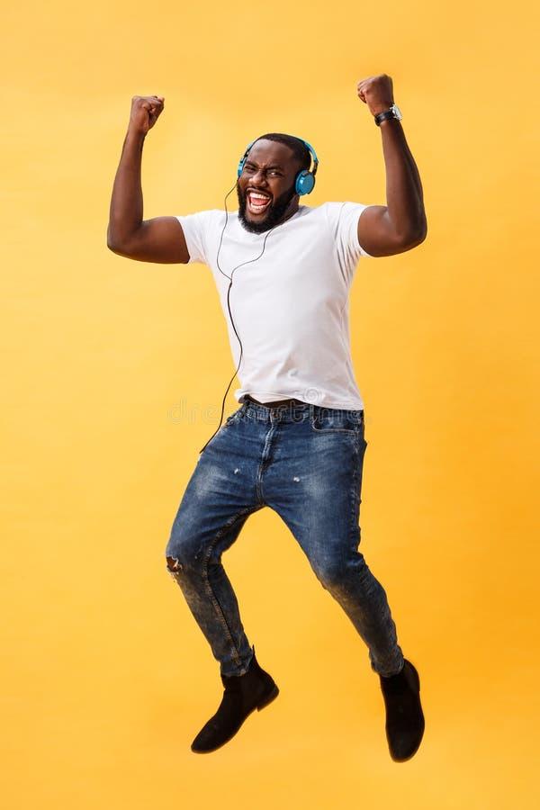 Retrato completo do comprimento de um homem afro-americano novo da cereja que escuta a música com fones de ouvido e a dança isola fotografia de stock
