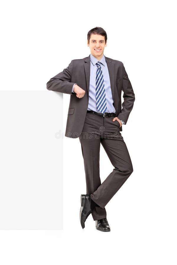 Retrato completo do comprimento de um homem de negócios novo que levanta em um painel imagem de stock royalty free