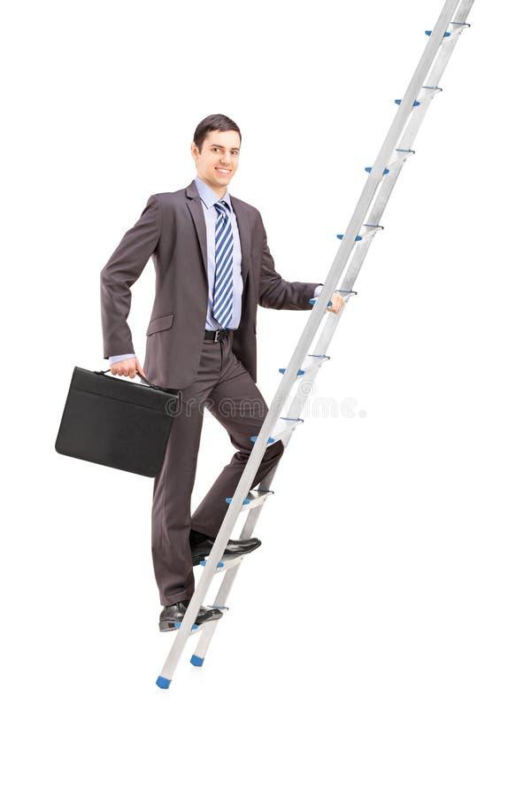 Retrato completo do comprimento de um homem de negócios que escala uma escada imagem de stock
