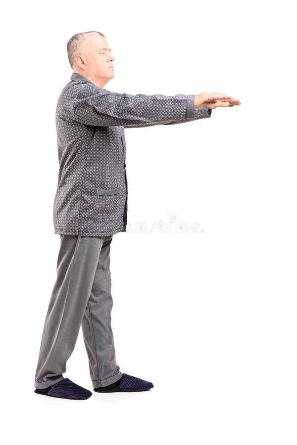 Retrato completo do comprimento de um homem maduro nos pijamas que sleepwalking fotografia de stock