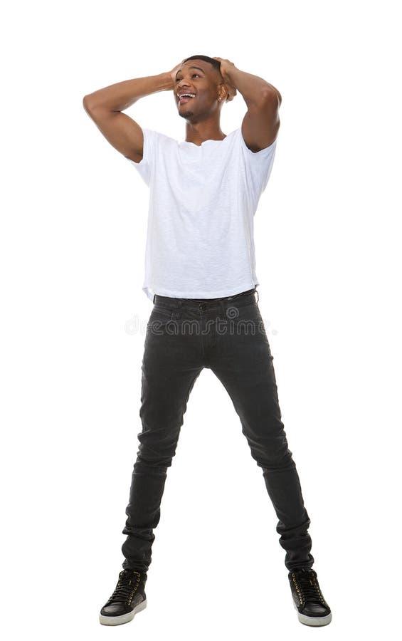 Retrato completo do comprimento de um homem novo com mãos na cabeça imagens de stock