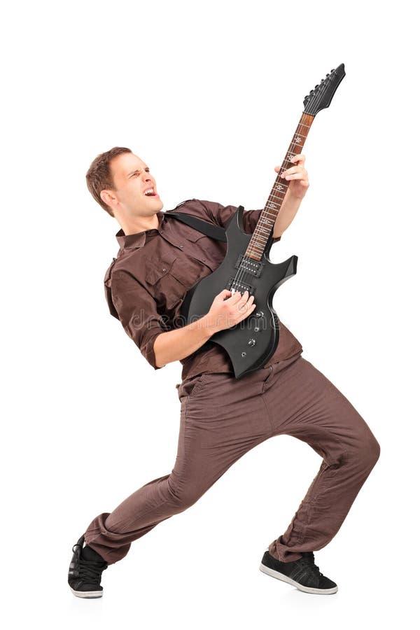 Retrato completo do comprimento de um homem novo que joga na guitarra elétrica imagem de stock