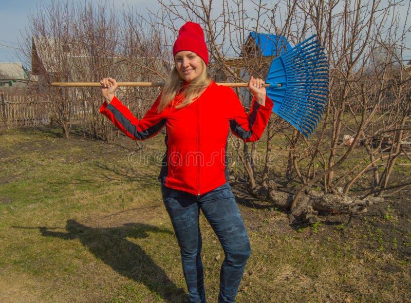 Retrato completo do comprimento de um jardineiro profissional de sorriso da mulher com um ancinho, um louro bonito que trabalha n imagem de stock