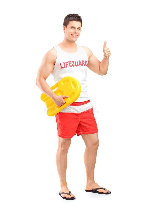 Retrato completo do comprimento de um lifeguard feliz no dever que dá um polegar fotos de stock