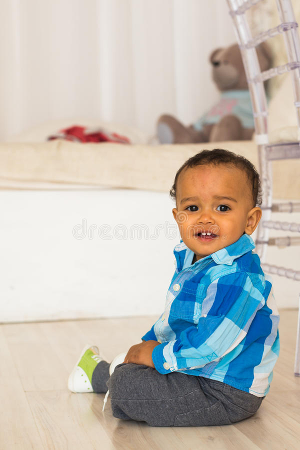 Retrato completo do comprimento de um menino novo da raça misturada que senta-se no assoalho imagem de stock royalty free