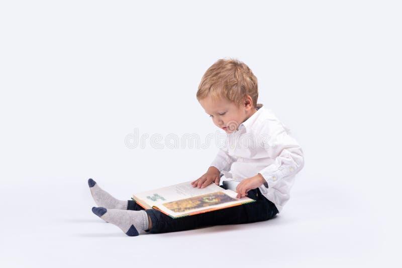 Retrato completo do comprimento de um menino sério pequeno com livro fotografia de stock