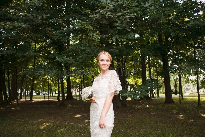 Retrato completo do comprimento de um par do recém-casado que guarda as mãos e que anda no parque imagens de stock royalty free