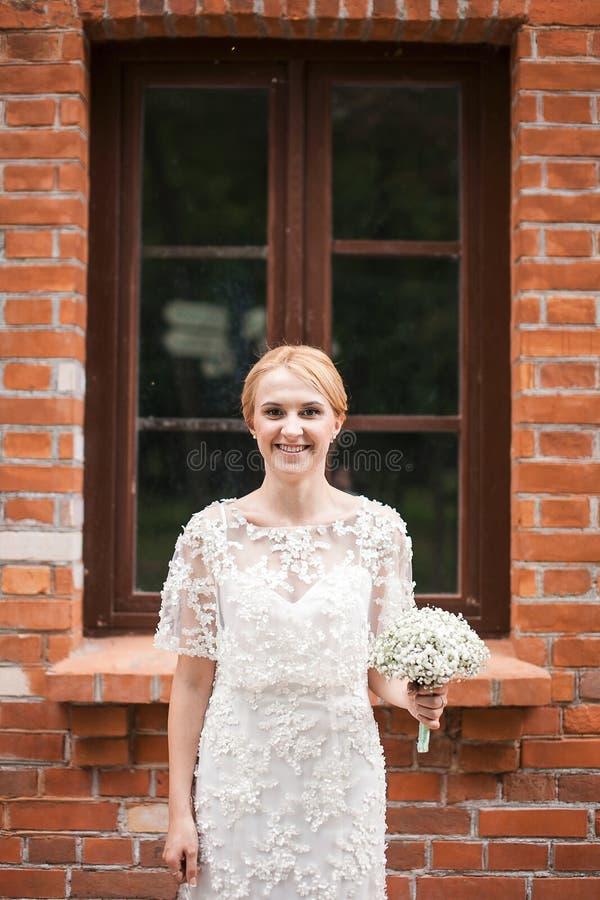 Retrato completo do comprimento de um par do recém-casado que guarda as mãos e que anda no parque fotos de stock