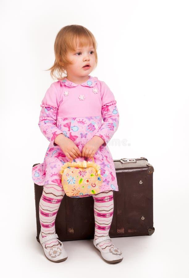 Retrato da rapariga adorável na mala de viagem velha fotografia de stock