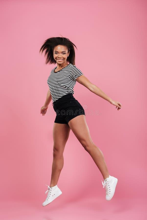 Retrato completo do comprimento de um salto africano alegre feliz da menina imagens de stock royalty free