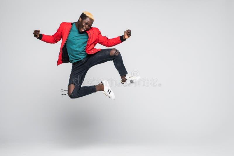 Retrato completo do comprimento de um salto afro-americano alegre do homem isolado em um fundo branco imagens de stock