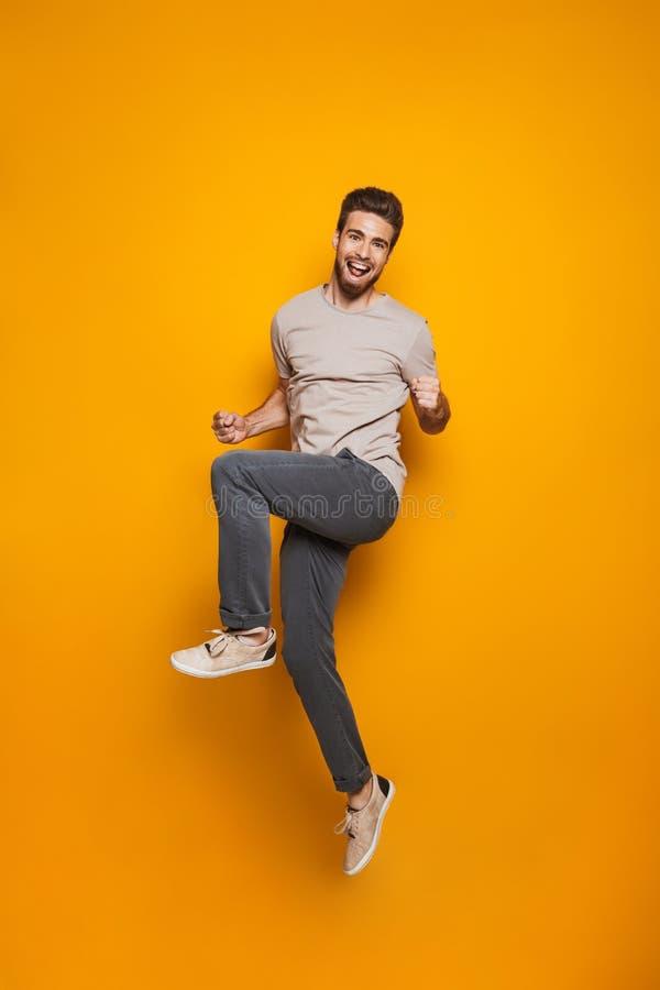 Retrato completo do comprimento de um salto alegre do homem novo fotos de stock royalty free