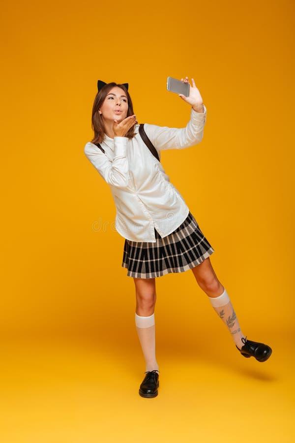 Retrato completo do comprimento de uma estudante adolescente bonito no uniforme fotos de stock