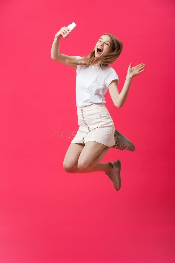 Retrato completo do comprimento de uma estudante adolescente entusiasmado no uniforme com tomada de um selfie ao saltar e ao most fotos de stock royalty free