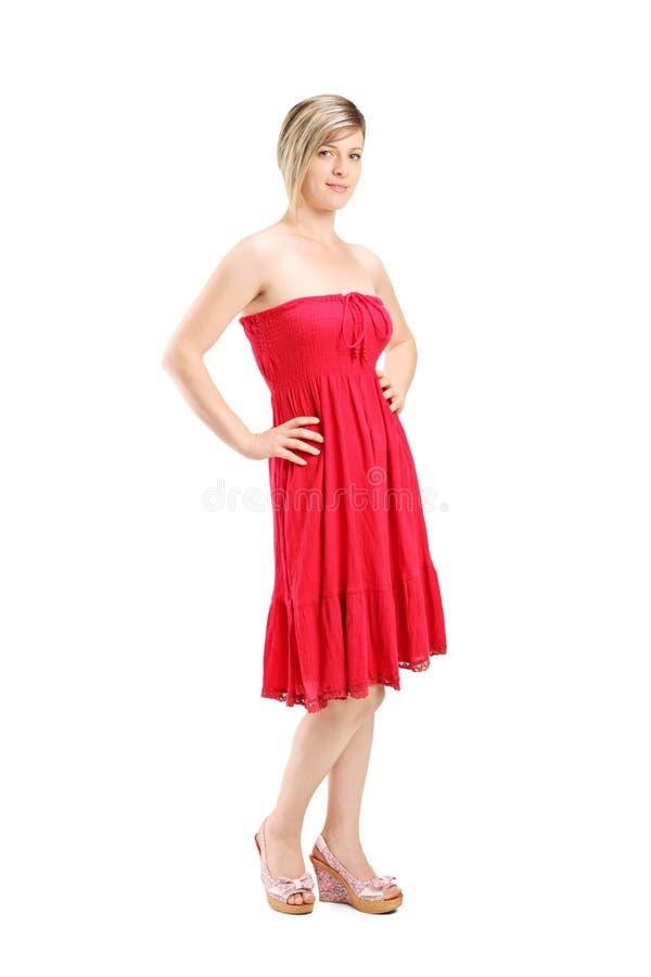 Retrato completo do comprimento de uma jovem mulher que levanta em um vestido vermelho imagens de stock