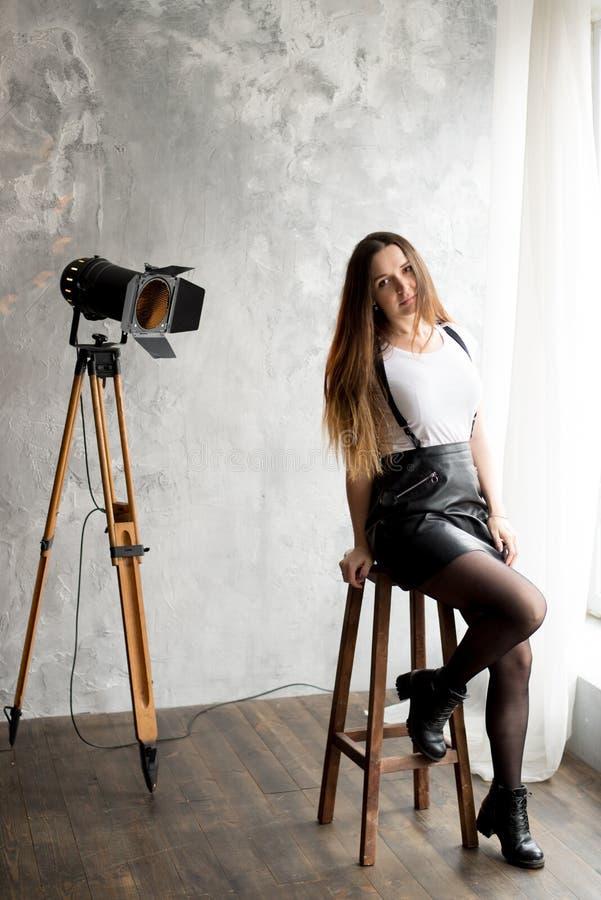 Retrato completo do comprimento de uma jovem mulher de sorriso que senta-se na cadeira fotografia de stock
