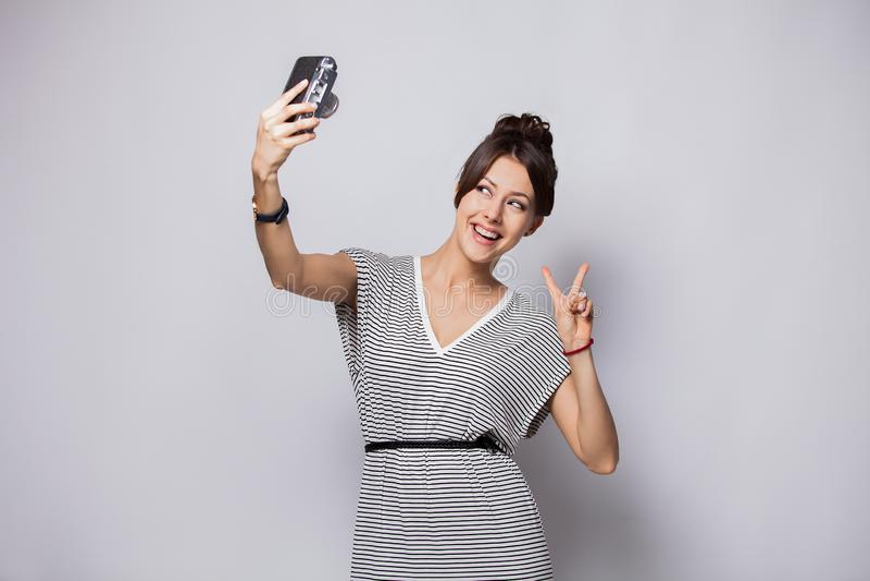 Retrato completo do comprimento de uma jovem mulher de sorriso que toma o selfie com a câmera isolada sobre o fundo branco fotografia de stock royalty free