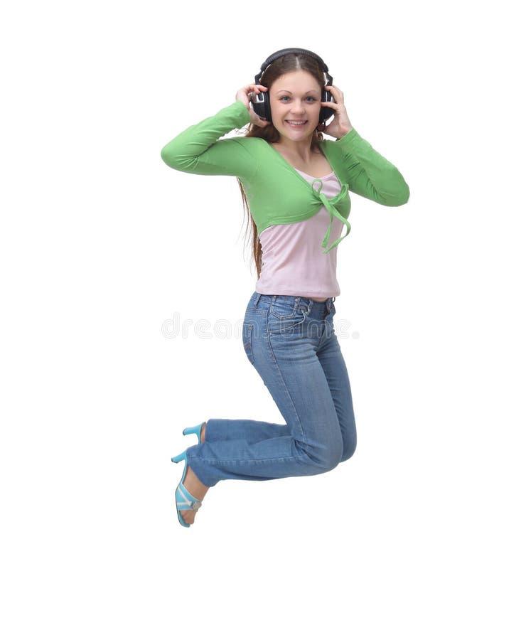 Retrato completo do comprimento de uma música de escuta da jovem mulher ocasional alegre com fones de ouvido e salto fotos de stock