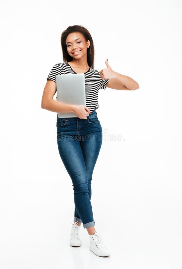 Retrato completo do comprimento de uma menina africana do adolescente que guarda o portátil fotografia de stock