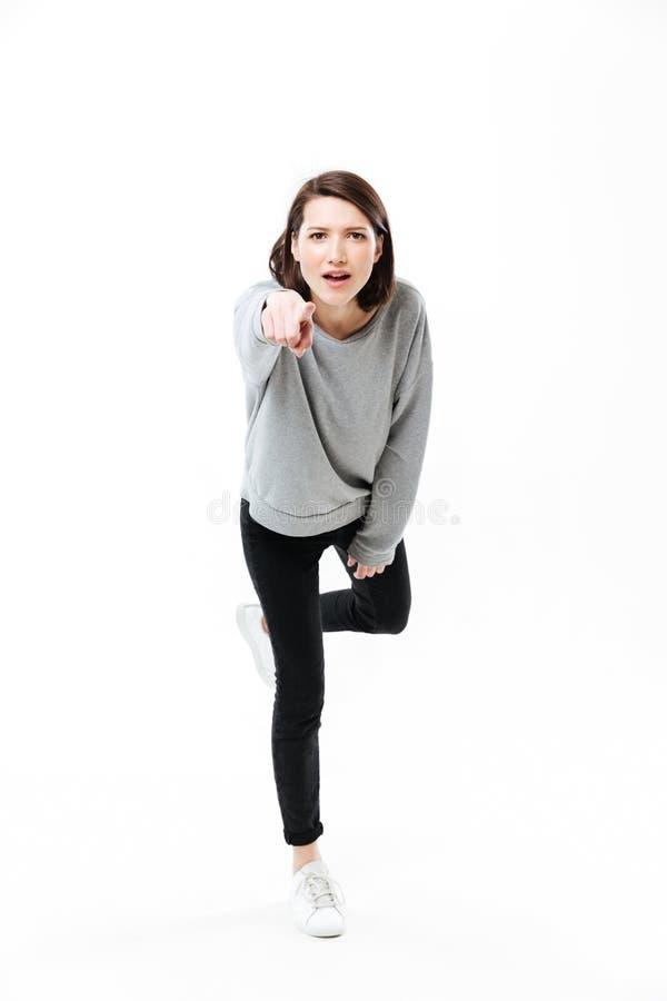 Retrato completo do comprimento de uma menina ocasional nova que está em uma mão e que aponta o dedo na câmera foto de stock