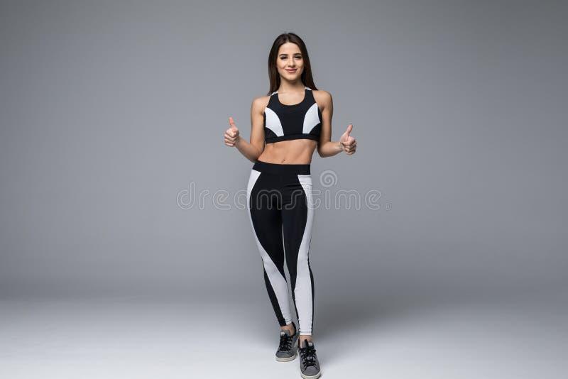 Retrato completo do comprimento de uma mulher desportiva feliz com polegares acima sobre o fundo cinzento olhando a câmera imagens de stock royalty free