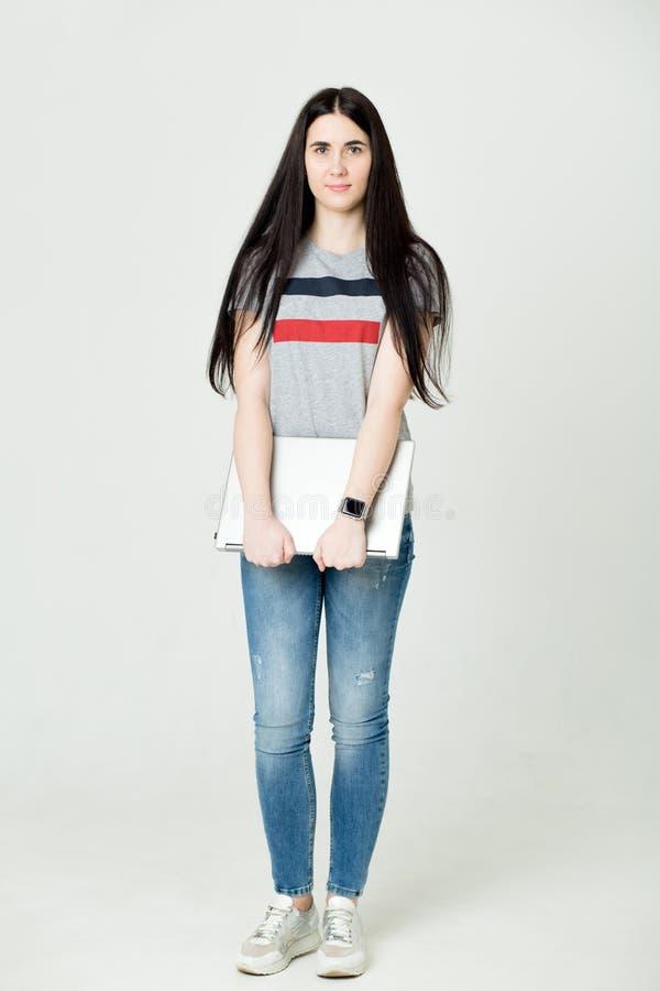 Retrato completo do comprimento de uma mulher feliz que usa o laptop isolado em um fundo branco foto de stock royalty free