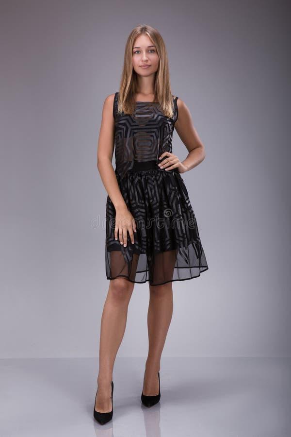 Retrato completo do comprimento de uma mulher loura bonita em pouco vestido preto da forma imagem de stock royalty free