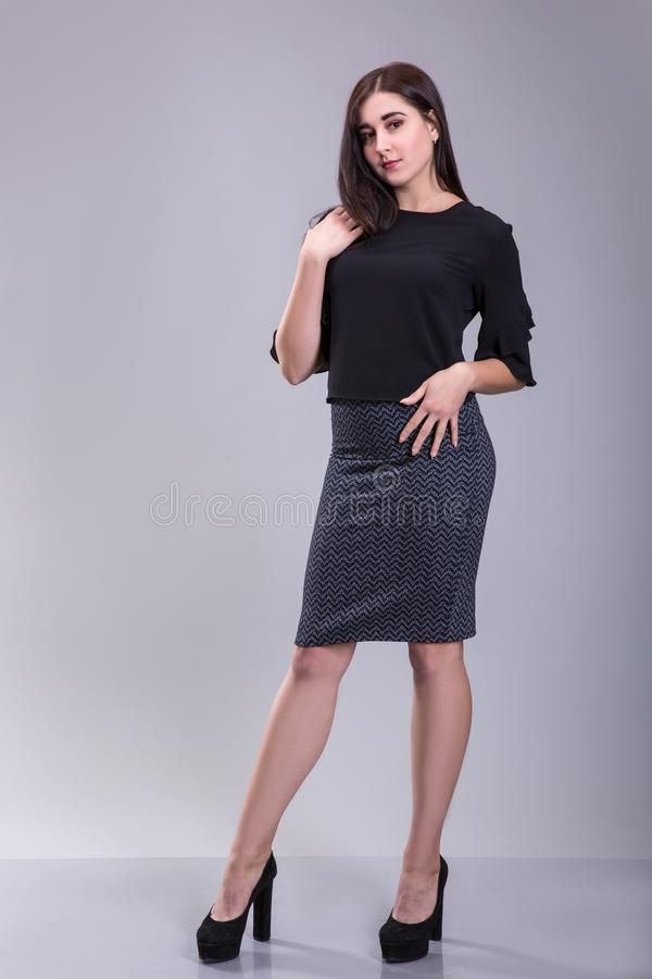 Retrato completo do comprimento de uma mulher na moda séria no vestido preto que está em um fundo cinzento fotos de stock royalty free
