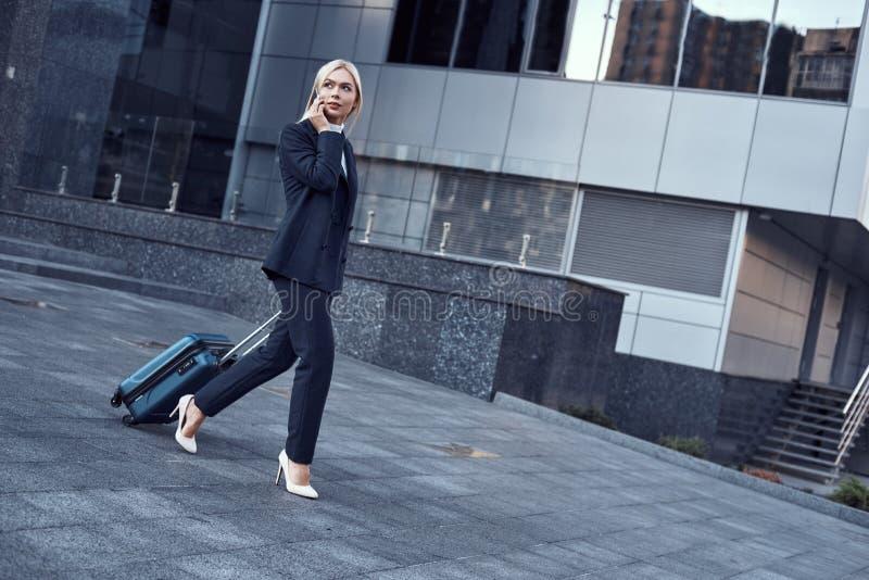 Retrato completo do comprimento de uma mulher de negócios bem sucedida de sorriso que puxa a mala de viagem fotos de stock
