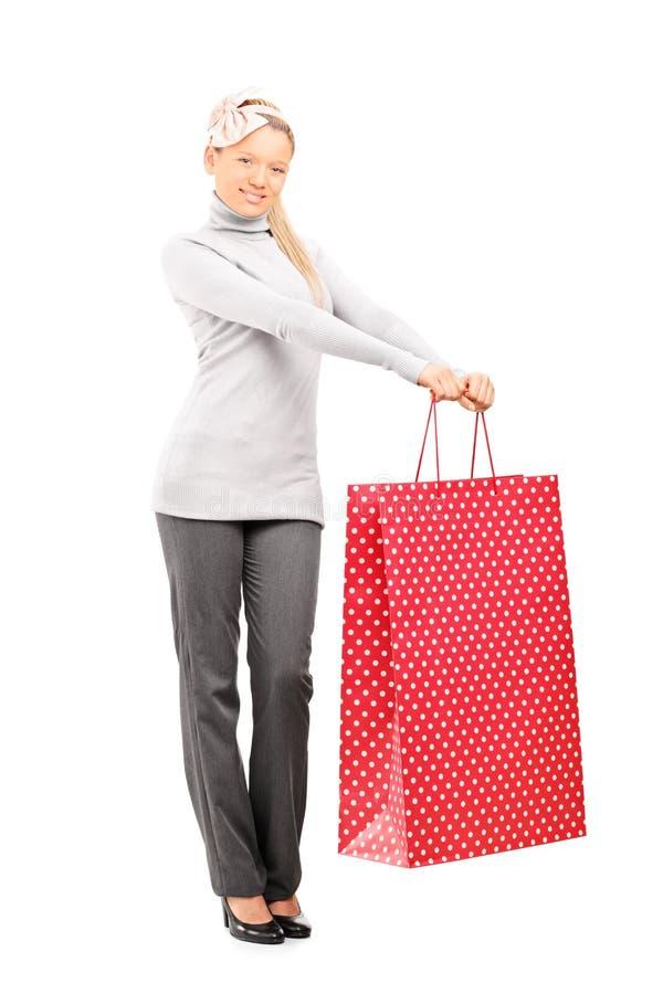 Retrato completo do comprimento de uma mulher que guarda um saco de compras grande foto de stock