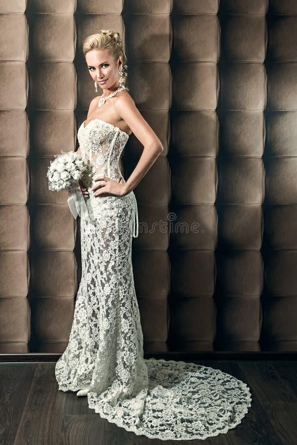 Retrato completo do comprimento de uma noiva bonita que guarda o ramalhete fotos de stock royalty free