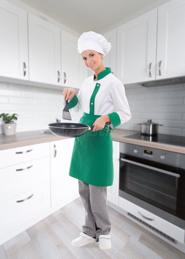 Retrato completo do comprimento do cozinheiro chefe da mulher na frigideira guardando uniforme imagem de stock royalty free